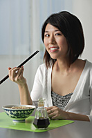 Young woman with chopsticks, eating a bowl of noodles - Asia Images Group