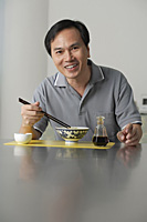 Mature man sitting and eating a bowl of noodles - Asia Images Group