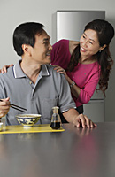 Mature man in kitchen, eating a bowl of noodles, turning to look at woman standing behind him - Asia Images Group