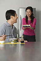Mature couple in kitchen, man sitting in front of a bowl of noodles, woman behind him holding a plate of food - Asia Images Group