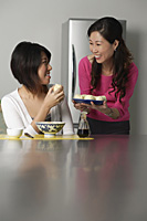 Mother and daughter in kitchen, older woman offering daughter a plate of Chinese buns - Asia Images Group