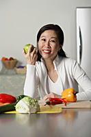 Woman in kitchen, holding an apple, vegetables on table around her - Asia Images Group