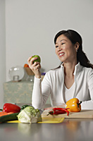 Woman in kitchen, looking at apple, vegetables on table around her - Asia Images Group