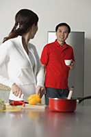 Mature woman in kitchen preparing a meal, turning to look man standing behind her - Asia Images Group