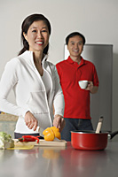 Mature woman in kitchen preparing a meal, man standing behind her, both looking at camera - Asia Images Group