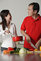 Couple in kitchen, preparing a meal together - Asia Images Group