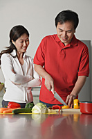 Couple in kitchen, man cutting vegetables, woman watching him - Asia Images Group