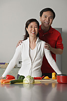 Mature couple in kitchen, smiling at camera - Asia Images Group