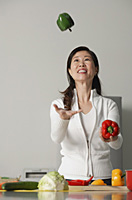 Woman in kitchen, juggling vegetables - Asia Images Group