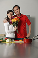 Mature couple in kitchen, embracing, woman holding bouquet of flowers - Asia Images Group