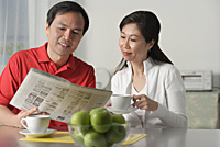 Mature couple at home, looking at newspaper and having coffee - Asia Images Group