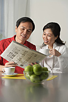Mature couple looking at newspaper and having coffee - Asia Images Group