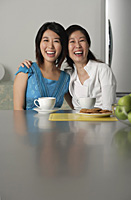 Mother and daughter at home, arms around each other, smiling - Asia Images Group