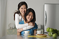 Mother embracing adult daughter, both smiling at camera - Asia Images Group