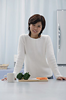 Woman in kitchen, smiling at camera - Asia Images Group