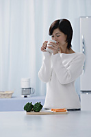 Woman in kitchen, drinking from a cup - Asia Images Group