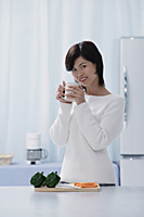 Woman in kitchen, holding a mug, looking at camera - Asia Images Group