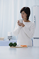 Woman in kitchen, holding mug, looking away - Asia Images Group