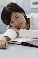 Woman leaning on book, smiling at camera - Asia Images Group