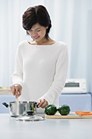 Woman in kitchen, cooking - Asia Images Group