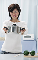 Woman in kitchen, holding crocking pot towards camera - Asia Images Group