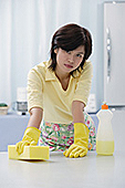 Woman in kitchen wearing gloves, cleaning kitchen counter with sponge - Asia Images Group