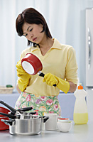 Woman in kitchen, cleaning pots and pans - Asia Images Group