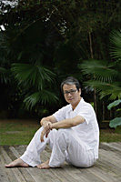 Mature man sitting outdoors in garden, looking at camera - Asia Images Group