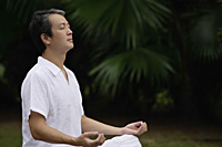 Mature man sitting outdoors, meditating - Asia Images Group