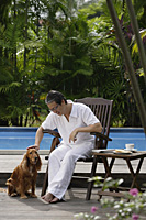 Mature man sitting by swimming pool, petting his dog - Asia Images Group