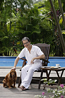 Mature man with his dog, sitting by swimming pool - Asia Images Group
