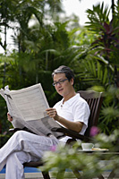 Mature man sitting in garden, reading newspaper - Asia Images Group
