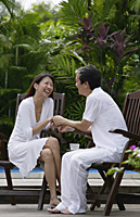 Couple sitting outdoors, face to face, holding hands - Asia Images Group