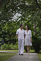 Couple walking along path in garden, looking at each other - Asia Images Group