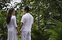 Couple in garden, holding hands, looking at each other - Asia Images Group