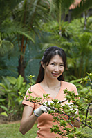 Woman in garden, pruning plant, smiling at camera - Asia Images Group