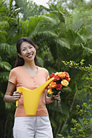 Woman in garden, holding bouquet of flowers and watering can - Asia Images Group