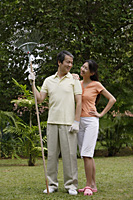 Couple standing side by side in garden, looking at each other, man holding garden rake - Asia Images Group