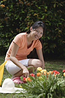 Woman tending to flower bed in garden - Asia Images Group
