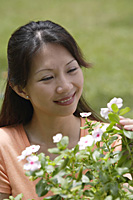 Woman outdoors, looking at flowering plants - Asia Images Group