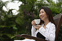Woman sitting outdoors, smiling, holding cup and saucer - Asia Images Group