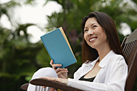 Woman sitting outdoors, reading a book, looking away - Asia Images Group