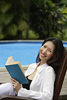 Woman sitting by swimming pool, holding a book, smiling at camera - Asia Images Group
