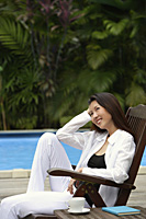 Woman sitting by swimming pool, hand on head, looking away - Asia Images Group