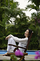 Woman outdoors, sitting by swimming pool - Asia Images Group