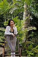 Woman in garden, leaning on chair, smiling at camera - Asia Images Group