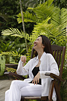 Woman sitting in garden, smiling, looking up - Asia Images Group