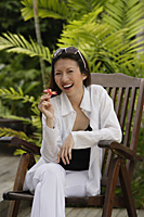 Woman sitting in garden, holding flower, smiling - Asia Images Group