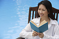 Woman by swimming pool, reading a book, looking away - Asia Images Group