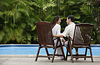Couple sitting by swimming pool,  looking at each other, rear view - Asia Images Group